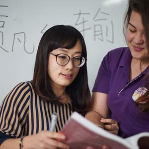 Student receives help during Chinese Class.